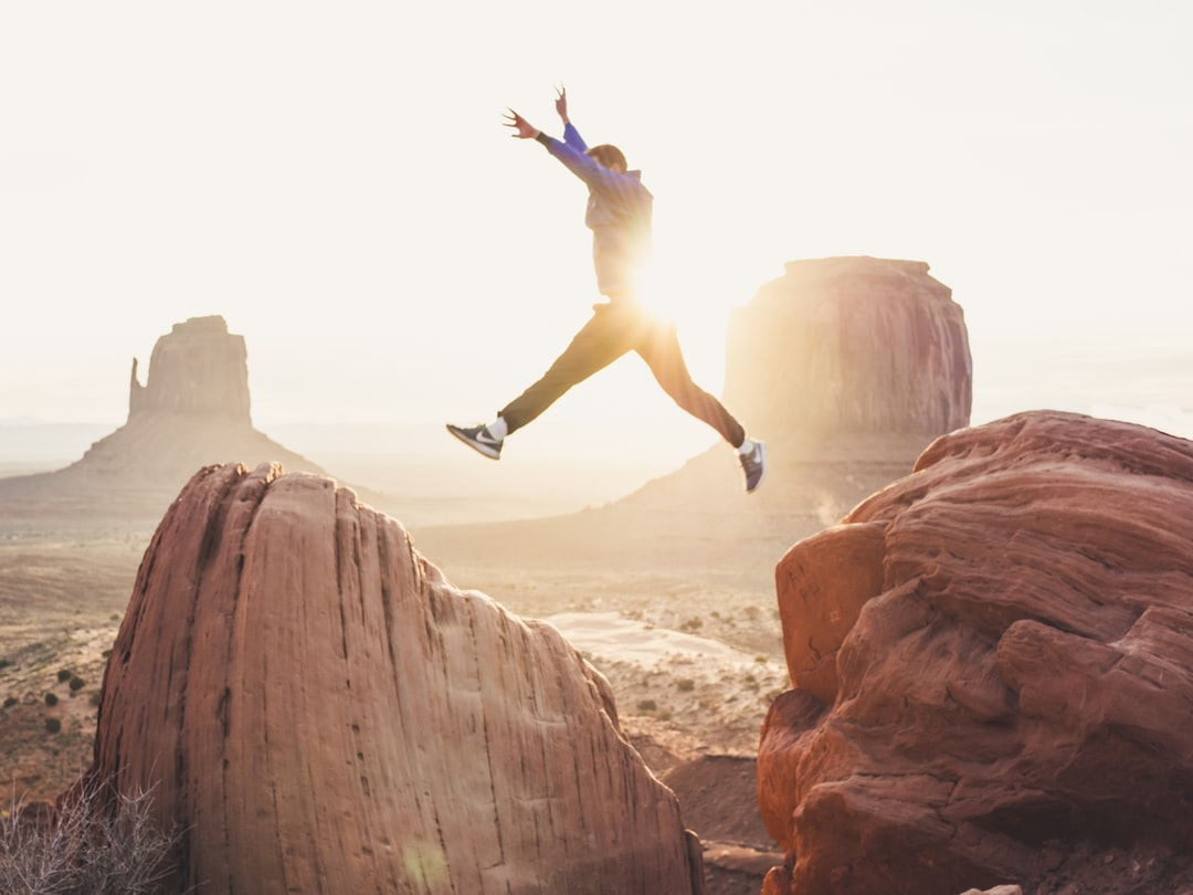 A person flying through the air on a rock